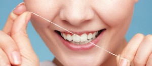 Part of female face. Young woman smiling girl cleaning her white teeth with dental floss on blue. Daily health care. Studio shot.